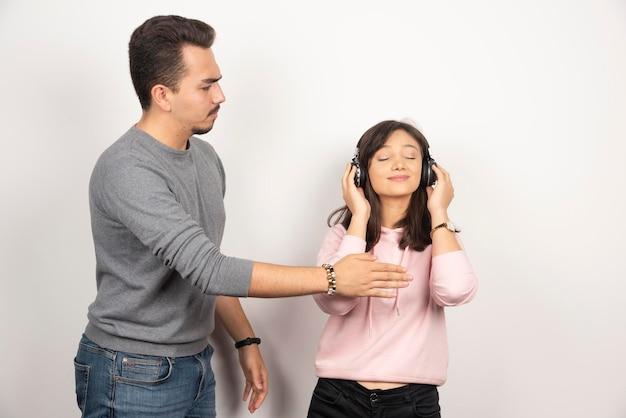 De jonge man wil vrouw met hoofdtelefoon tegenhouden.