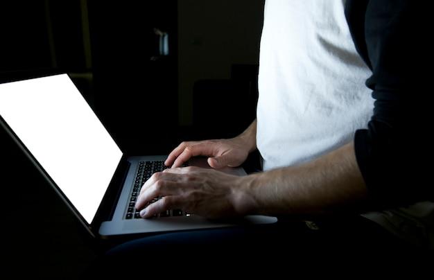 De jonge man zittend op de bank met moderne laptop in de avond en surfen op het web