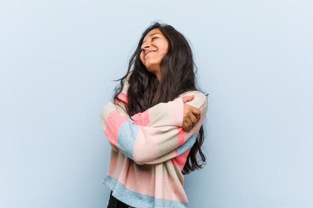 De jonge manier indische vrouw koestert zich, glimlachend zorgeloos en gelukkig.