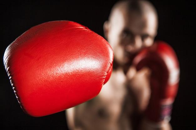 De jonge mannelijke atleet kickboksen op een zwarte achtergrond