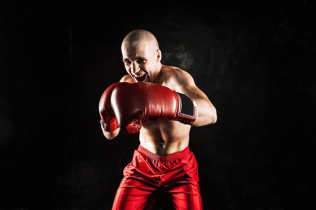 De jonge mannelijke atleet kickboksen op een zwarte