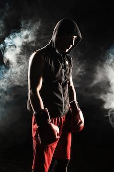 De jonge mannelijke atleet kickboksen staande op een achtergrond van blauwe rook