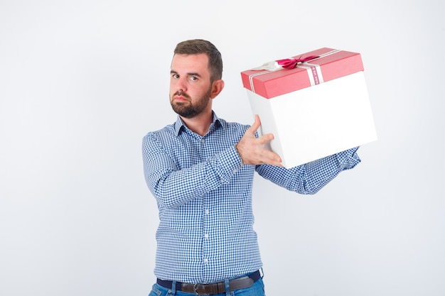 De jonge mannelijke doos van de holdingsgift in overhemd en op zoek gericht, vooraanzicht.