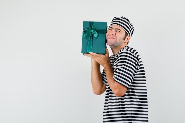 De jonge mannelijke doos van de holdingsgift in t-shirt, hoed en op zoek gelukkig.