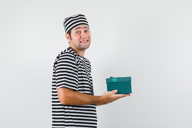 De jonge mannelijke doos van de holdingsgift in t-shirt, hoed en vrolijk kijkt.
