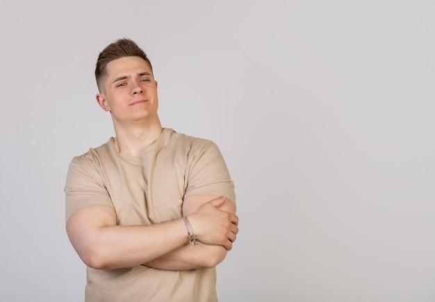 De jonge mannelijke kerel sloeg zijn armen over zijn borst met een gemiddelde uitdrukking op zijn gezicht