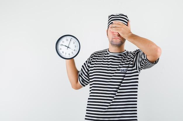 De jonge mannelijke klok van de holdingsmuur in t-shirt, hoed en het kijken vergeetachtig, vooraanzicht.