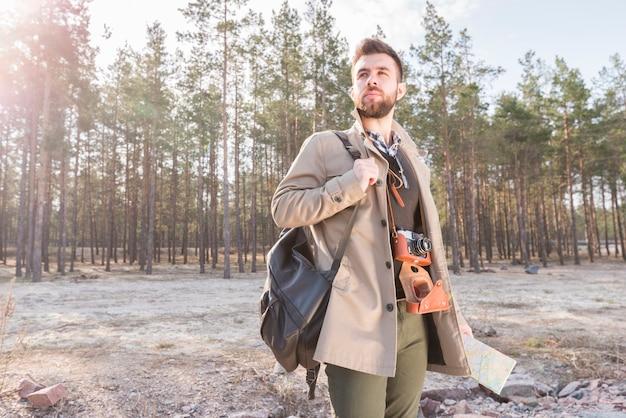 De jonge mannelijke rugzak van de reizigersholding op zijn schouder en kaart die zich in het bos bevinden