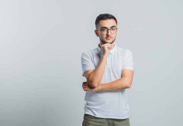 De jonge mannelijke steunende kin dient wit t-shirt, broek in en kijkt peinzend
