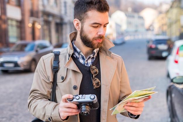 De jonge mannelijke toerist die een weg met een kaart in van hem zoeken dient de stad in