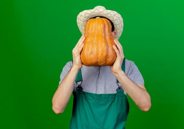 De jonge mannelijke tuinman die het tuinieren hoed draagt houdt pompoen voor gezicht dat op groene achtergrond met exemplaarruimte wordt geïsoleerd