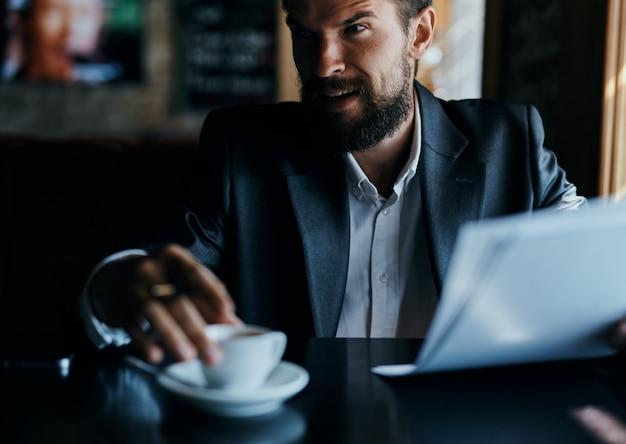 De jonge mannelijke zakenman zit bij een lijst met documenten en drinkt koffie