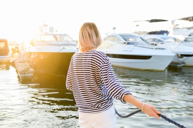 De jonge mariene stijlvrouw zit op de boot en kijkt vooruit