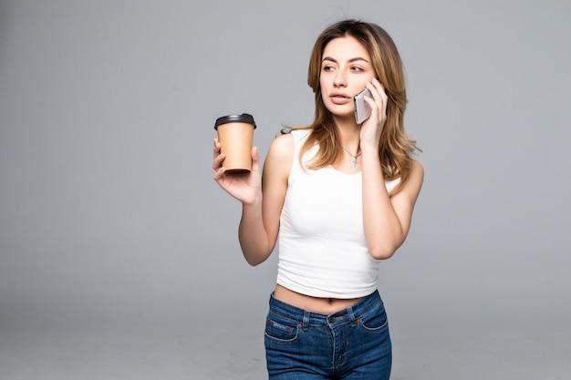 De jonge meeneemkoffiekop van de meisjesholding terwijl spreken op smartphone geïsoleerd op grijze muur