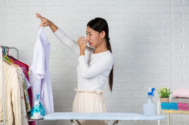 De jonge meid die stinkt, de geur van het afgewerkte shirt op de witte baksteen.