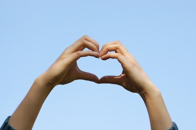 De jonge meisjeshanden die handen in hartvorm met de duidelijke blauwe hemelachtergrond houden