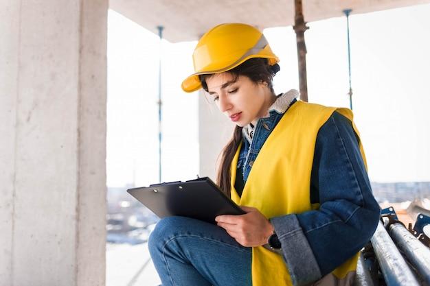 De jonge meisjesingenieur in een beschermende helm vult document bij een bouwwerf