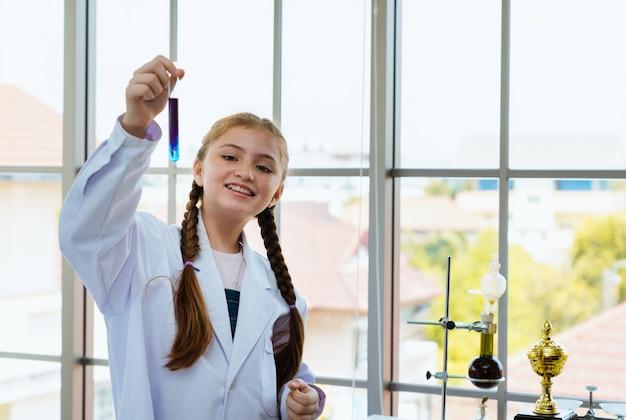 De jonge meisjeswetenschapper toont chemisch gemengd in glazen buis in de laboratoriumruimte
