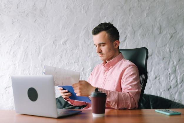 De jonge mens analyseert sommige documenten bij het werkplaatsbureau