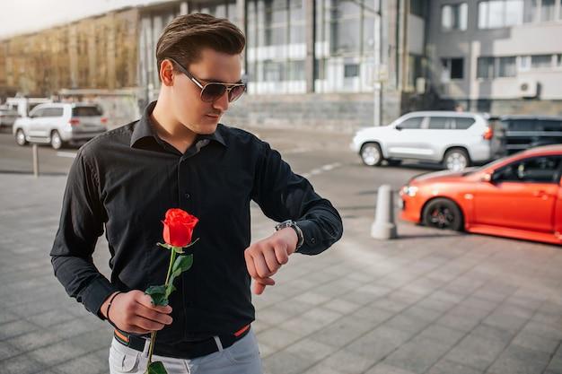 De jonge mens bevindt zich buiten op straat en houdt rode roos. hij kijkt naar horloges. guy wacht. er is een weg met auto's achter hem.