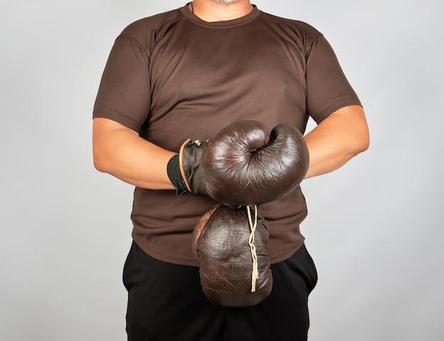 De jonge mens bevindt zich en zet op zijn handen zeer oude uitstekende bruine bokshandschoenen