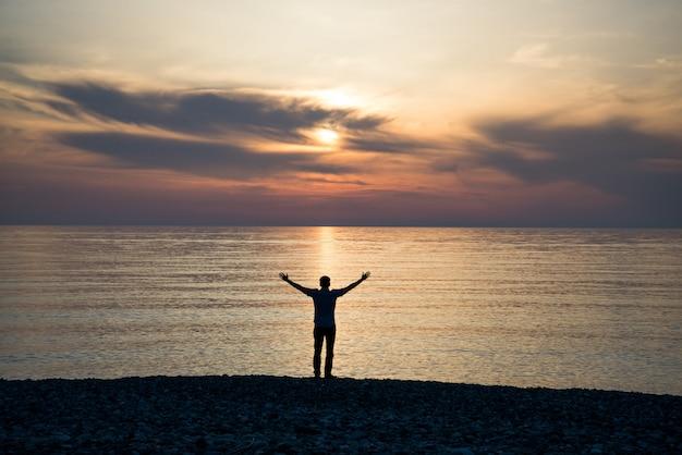 De jonge mens bij zonsondergang heft zijn handen op
