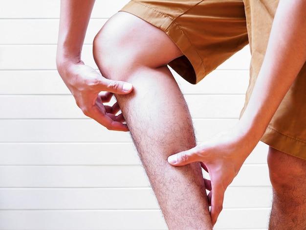 De jonge mens die aan beenpijn en spieren lijden, gebruikt hand om op lichaam, medisch symptoom en gezondheidszorgconcept te masseren.