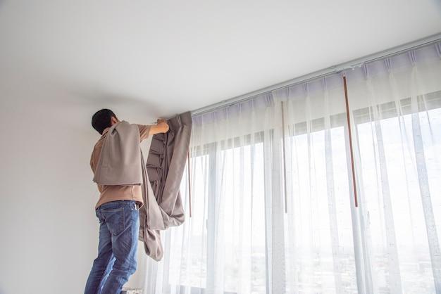 De jonge mens die blinde gordijnen over venster installeren vernieuwt binnen huis.