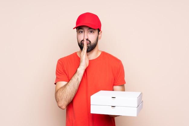 De jonge mens die een pizza over geïsoleerd houdt houdt palm samen. persoon vraagt om iets