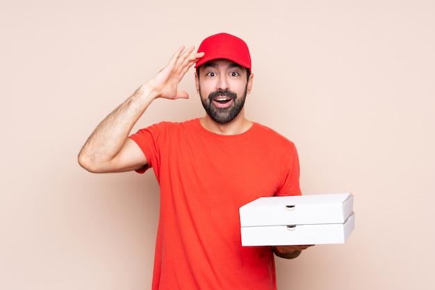 De jonge mens die een pizza over geïsoleerde achtergrond houdt heeft net iets gerealiseerd en heeft de oplossing voor ogen