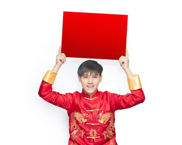 De jonge mens die een rode jurk met mandarijnkraag draagt, houdt het lege papieren aanplakbiljet boven zijn hoofd.