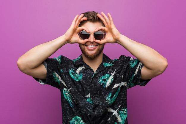 De jonge mens die een vakantie draagt kijkt het tonen van ok teken over ogen