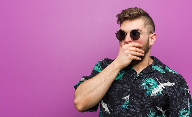 De jonge mens die een vakantie draagt kijkt nadenkend kijkend aan een exemplaar ruimte die mond behandelt met hand.