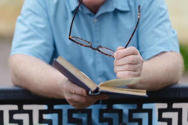 De jonge mens die en een boek openen lezen, sluit omhoog.