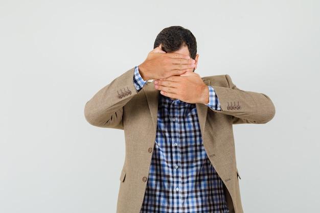 De jonge mens die gezicht behandelt met dient overhemd, jasje in en kijkt beschaamd. vooraanzicht.
