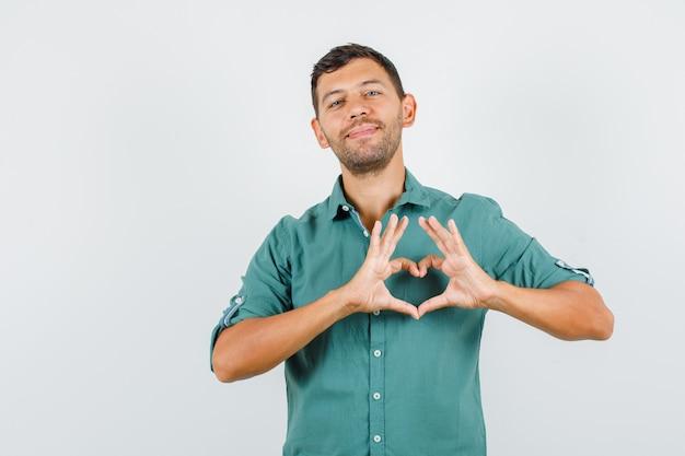 De jonge mens die hartvorm met handen in overhemd maakt en vriendschappelijk kijkt.