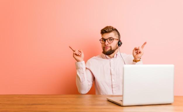 De jonge mens die in een call centre werkt wijst zijdelings, probeert tussen twee opties te kiezen.