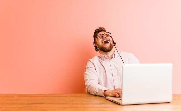 De jonge mens die in een call centre werkte ontspande en het gelukkige lachen, uitgerekte hals tonend tanden.