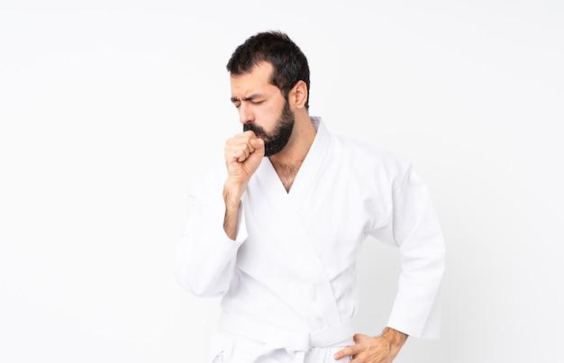 De jonge mens die karate over geïsoleerde witte achtergrond doet lijdt aan hoest en voelt slecht