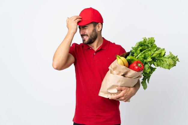 De jonge mens die met baard een zakhoogtepunt van groenten houdt die op witte muur wordt geïsoleerd die twijfels heeft met verwart gezichtsuitdrukking