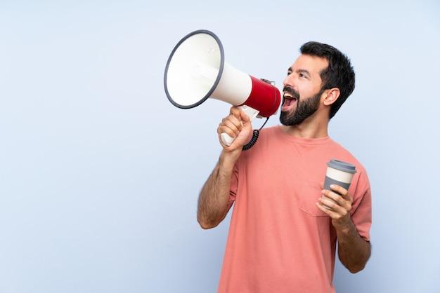 De jonge mens die met baard houden haalt koffie op blauw weg schreeuwend door een megafoon