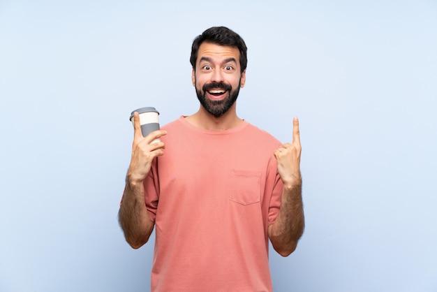 De jonge mens die met baard houdt haalt koffie over geïsoleerd blauw weg benadrukkend een groot idee