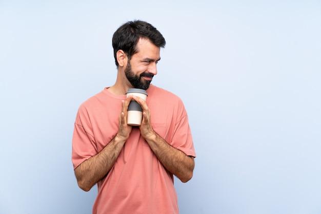De jonge mens die met baard houdt haalt koffie over geïsoleerde blauwe achtergrond weg die iets plannen