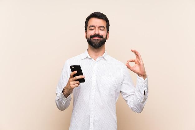 De jonge mens die met baard mobiel in zen houden stelt