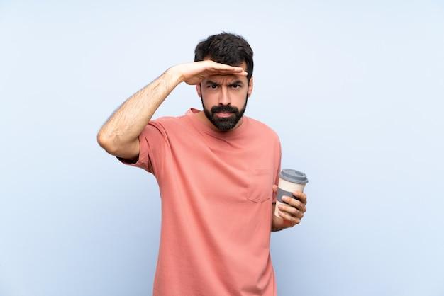 De jonge mens die met baard neemt haalt koffie op blauw weg kijkend ver weg met hand om iets te kijken