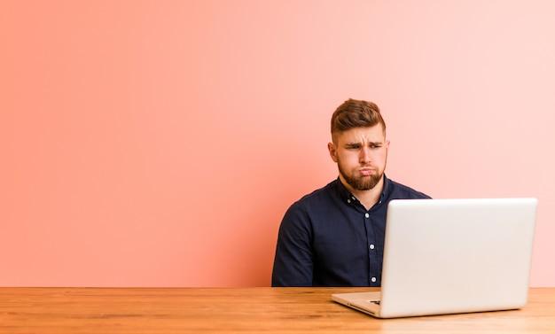 De jonge mens die met zijn laptop werkt blaast wangen, heeft uitdrukking vermoeid. gezichtsuitdrukking .