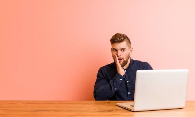 De jonge mens die met zijn laptop werkt zegt een geheim heet remmend nieuws en kijkt opzij