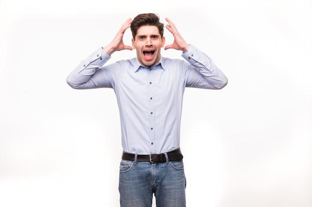 De jonge mens die open mond gilt, houdt hoofdhand, draagt toevallig blauw overhemd, geïsoleerde witte ruimte.