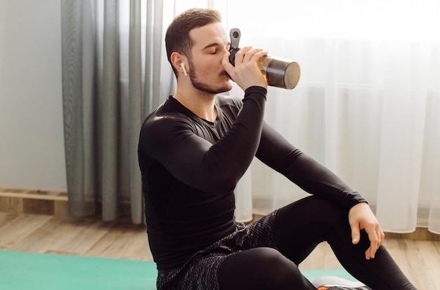 De jonge mens die sport maakt oefent thuis uit