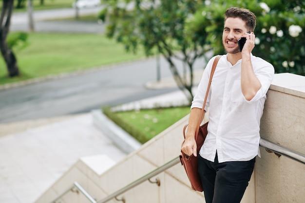 De jonge mens die van cherful zich buiten bevindt en telefoontje van vriend of familielid beantwoordt